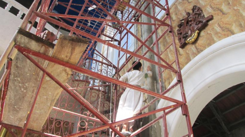 Brother, high up on the scaffolding, preparing the columns for gold leafing